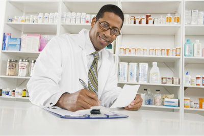 pharmacist writing with medicines at the background
