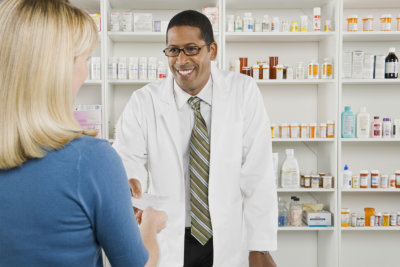 pharmacist handling paper to customer