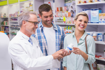 pharmacist assisting couple on choosing medicine